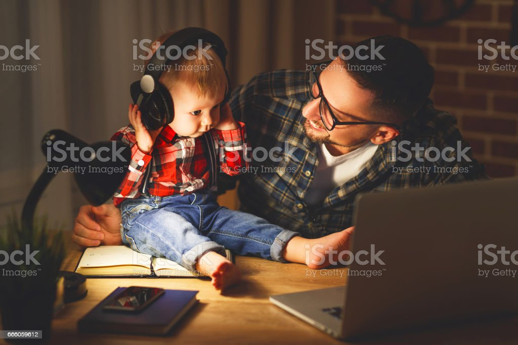 family father and son baby listening to music with headphones stock photo