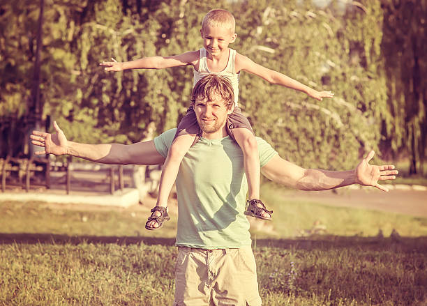 Vater Sohn Familie Mann und Junge sitzt auf den Schultern im Freien – Foto