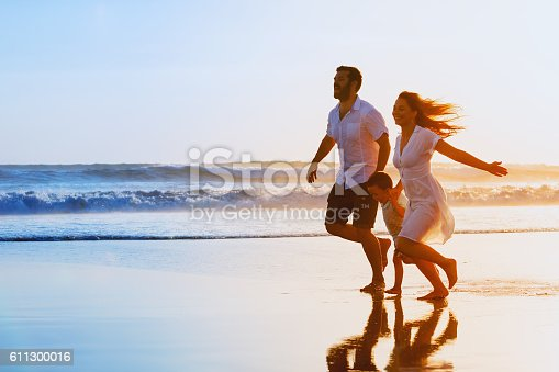 istock Family - father, mother, baby run on sunset beach 611300016