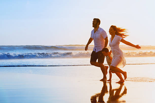Family - father, mother, baby run on sunset beach - fotografia de stock