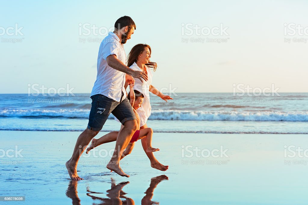Family - father, mother, baby run on sunset beach - foto de stock