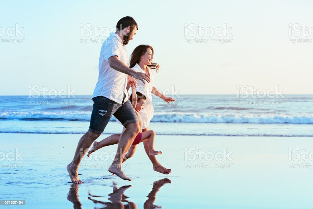 Family - father, mother, baby run on sunset beach stock photo