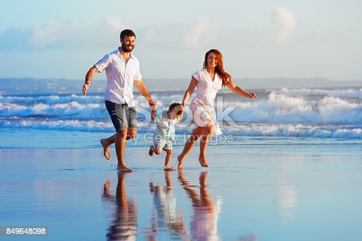 istock Family - father, mother, baby run on sunset beach 849648098