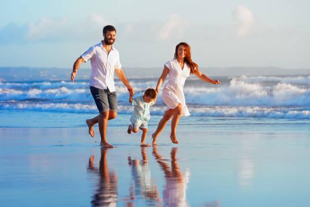 familie - vater, mutter, baby laufen am sunset beach - lustige babybilder stock-fotos und bilder