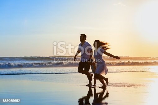 849648098 istock photo Family - father, mother, baby run on sunset beach 883065652