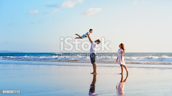 istock Family - father, mother, baby walk on sunset beach 849092112
