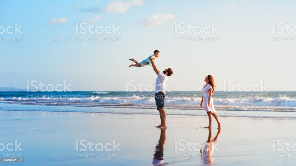 Family - father, mother, baby walk on sunset beach stock photo