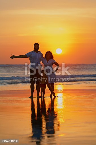 849648098 istock photo Family - father, mother, baby walk on sunset beach 884298260