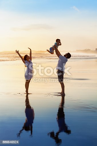 istock Family - father, mother, baby walk on sunset beach 886646524