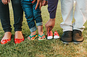 Family feet and legs posing for baby annoncement
