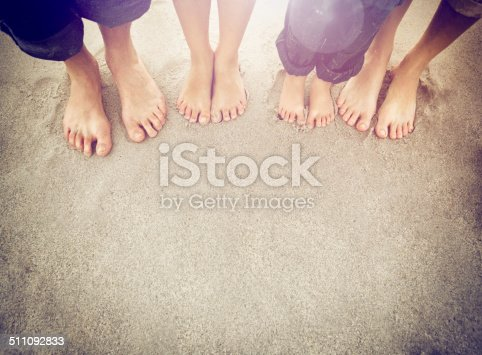 Family feet standing on the sand at the beach