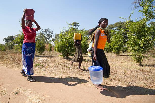 Família buscando água com baldes na zona rural do sul da África. - foto de acervo