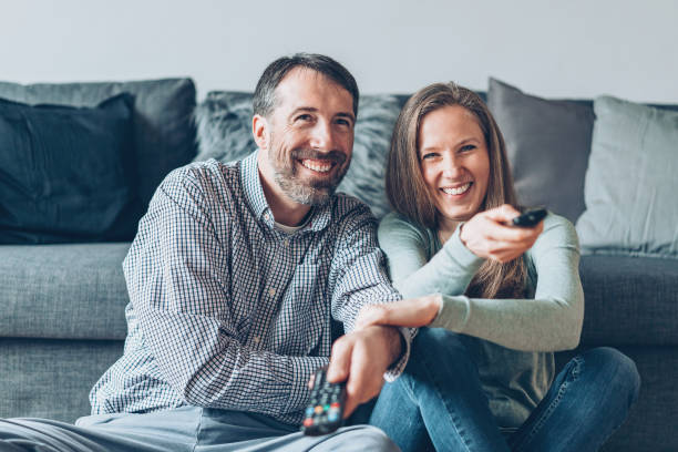 Family fighting for TV channels Happy family with TV remote controls changing channels stock pictures, royalty-free photos & images