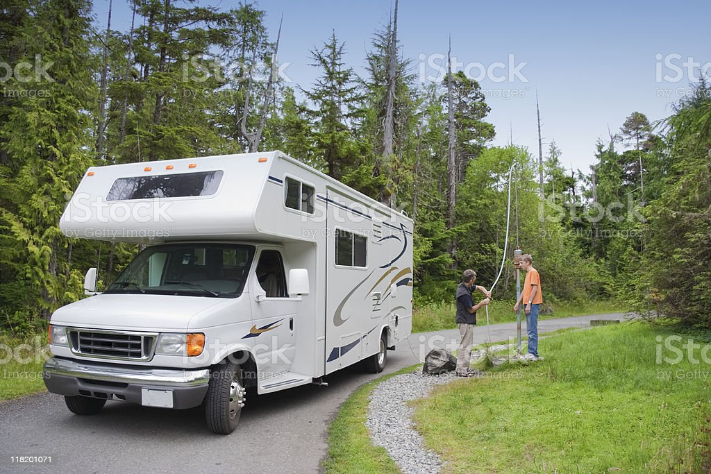 Family filling Freshwater in Motor Home at Dumping Station stock photo