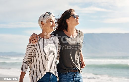 Shot of a young woman going for a walk along the beach with her elderly mother
