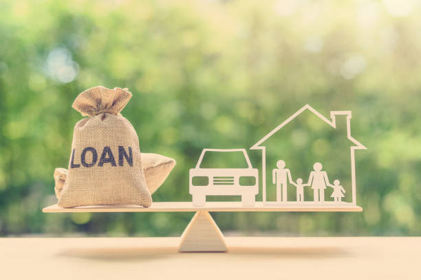 Family financial management, mortgage and payday loan or cash advance concept : Loan bags, family in a house on balance scale, depicts short term borrowing, high interest rate based on credit profile stock photo