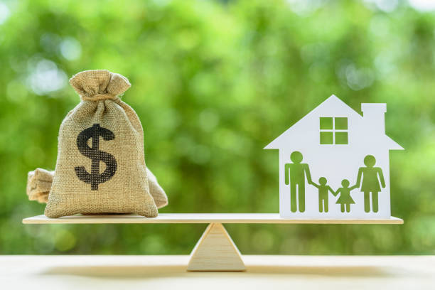 Family financial management, mortgage and payday loan or cash advance concept : Dollar bags, 4 members family under a house or shelter on a balance scale, depicts short term borrowing for a residence. - foto stock