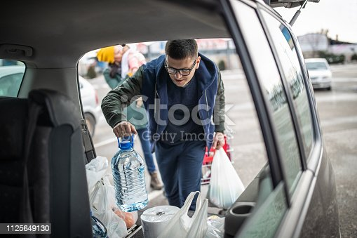 Family is loading car trunk with groceries the bought at the supermarket