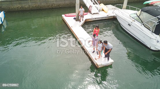 Filipino family fishing off dock at marina