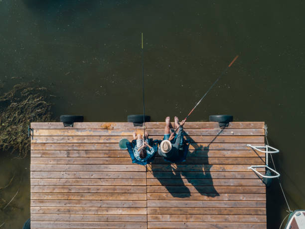 Family Fishing on Jetty Family spending time together, Father and son fishing on jetty by the lake. Directly above. freshwater fishing stock pictures, royalty-free photos & images