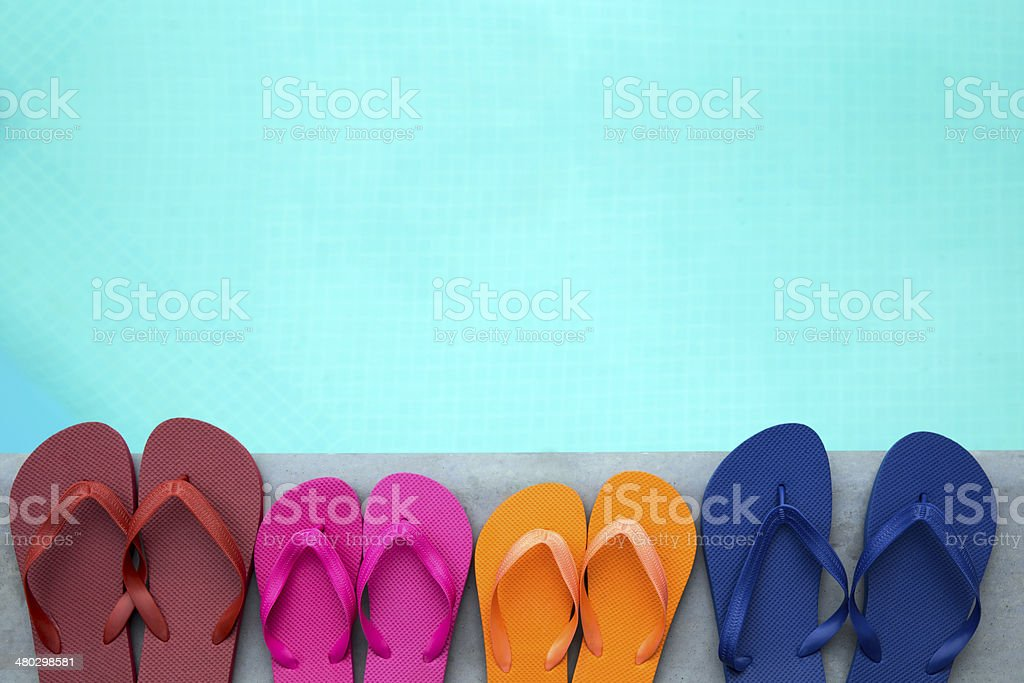 Row of colorful flip flops on grey stone at the pools\' edge. Flip...