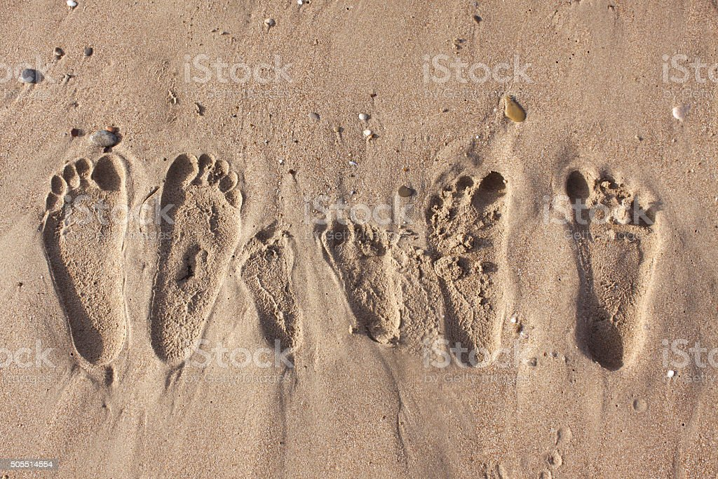 Family footprints on the sand beach stock photo