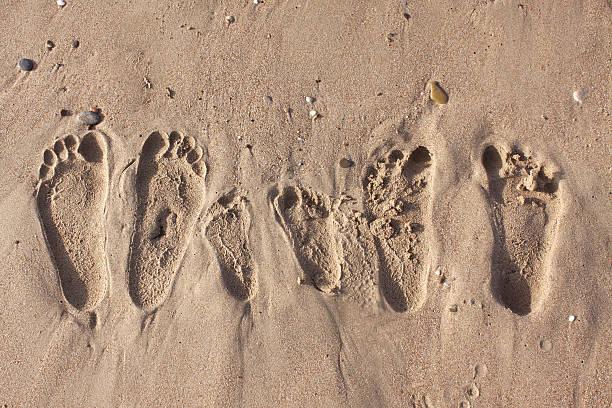 familien-fußspuren im sand beach - fußspuren stock-fotos und bilder