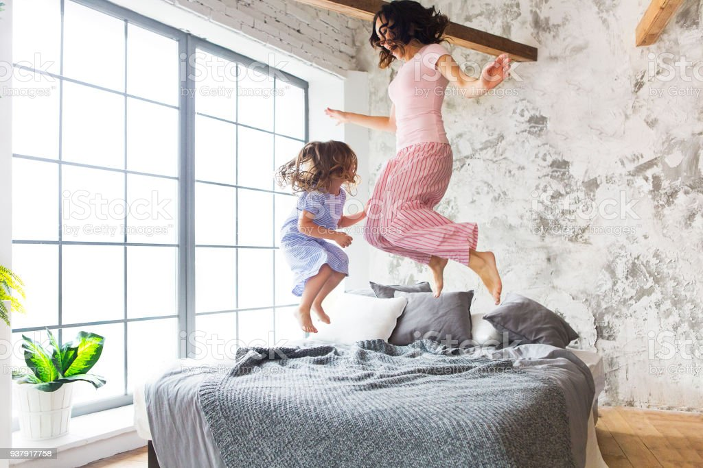 Family fun. Mother and daughter jumping on the bed stock photo