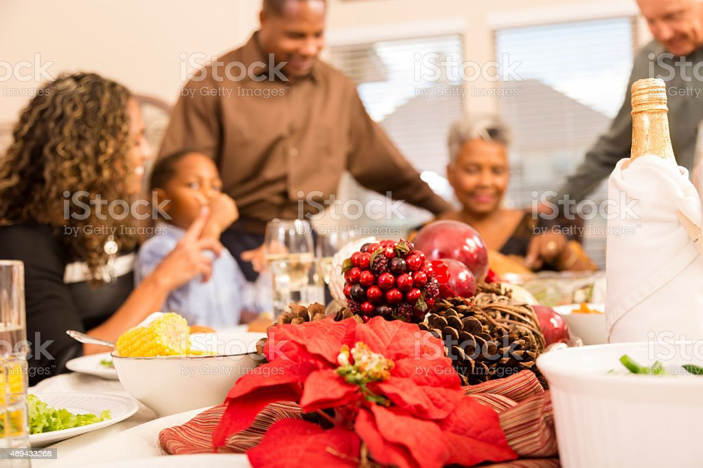 Family gather around the dinner table at Christmas time. stock photo