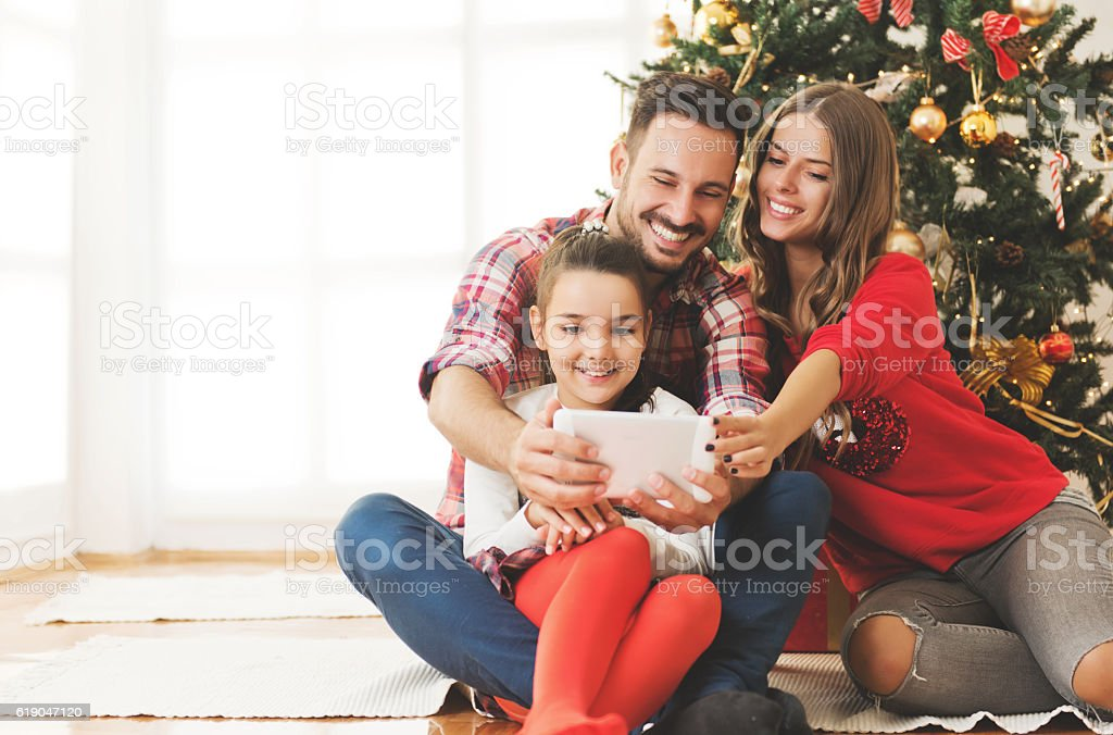 Family gathered around a Christmas tree, using a tablet – Foto