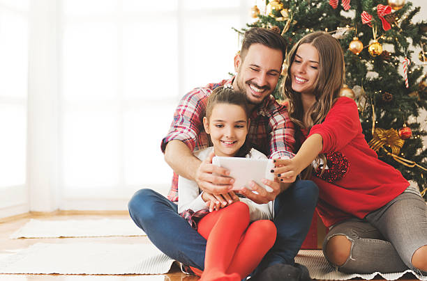 family gathered around a christmas tree, using a tablet - christmas families stock photos and pictures