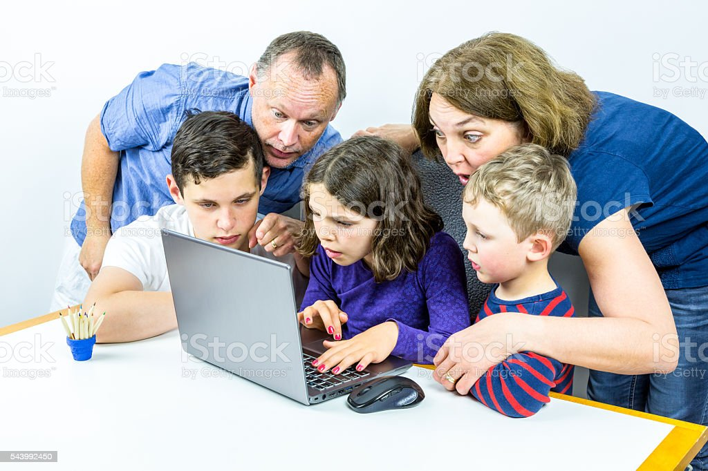 Family gathered around laptop. stock photo