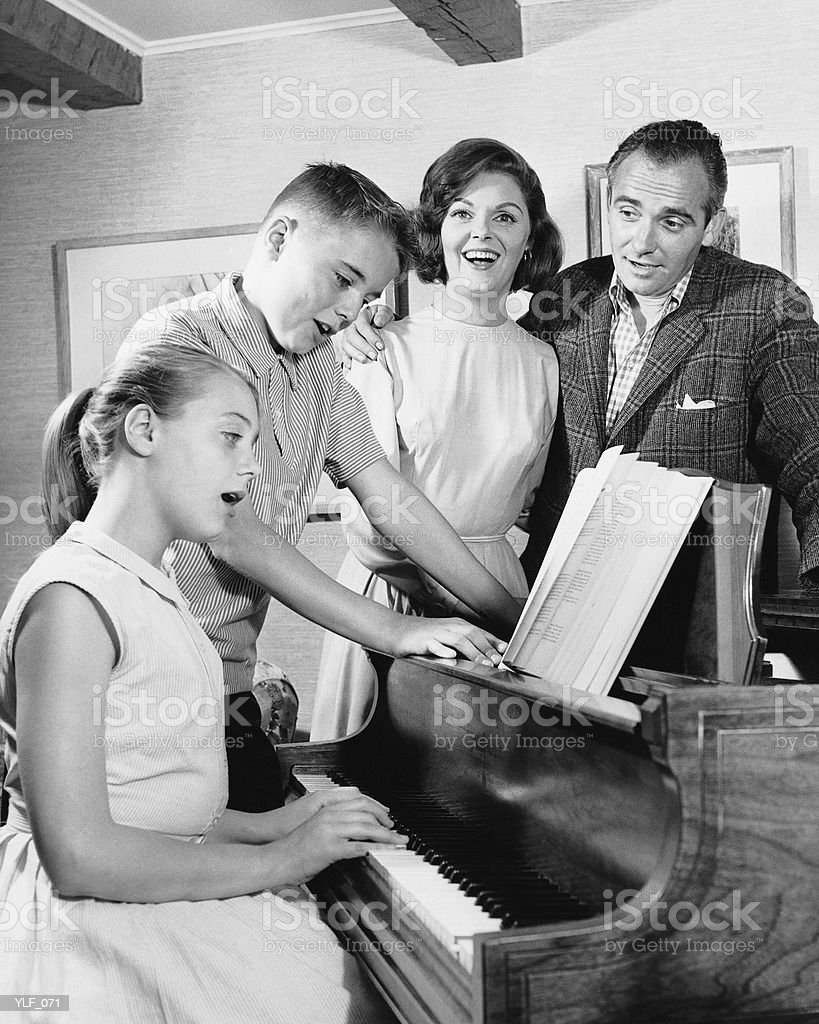 Family gathered around piano, singing 免版稅 stock photo