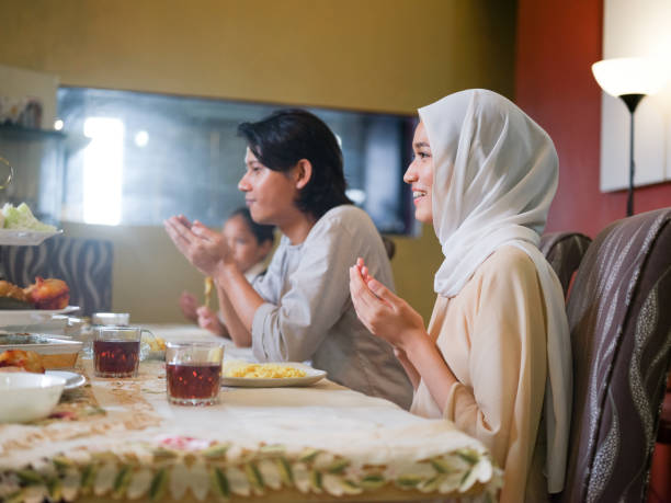 family gathering and eating together - скромная одежда стоковые фото и изображения