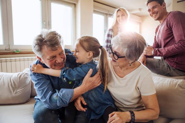 family gathering at sofa - pais e filhos imagens e fotografias de stock