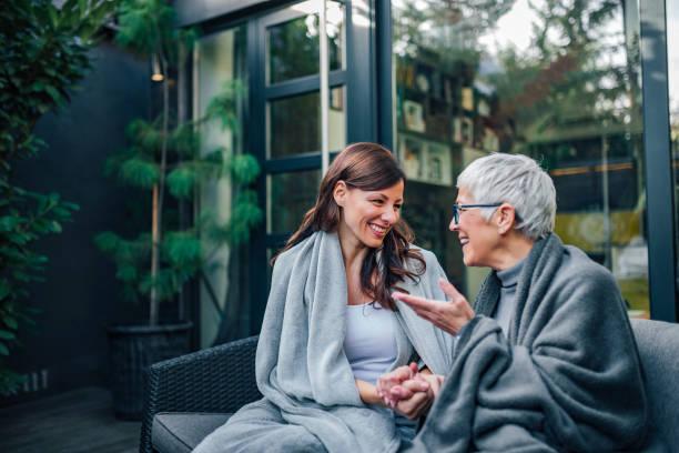 concepto de reunión familiar. dos mujeres de diferentes edades hablando en el patio de la casa moderna. - hija fotografías e imágenes de stock