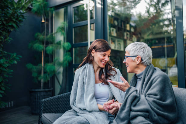 family gathering concept. two women of different age talking on the patio of modern house. - filhos adultos imagens e fotografias de stock