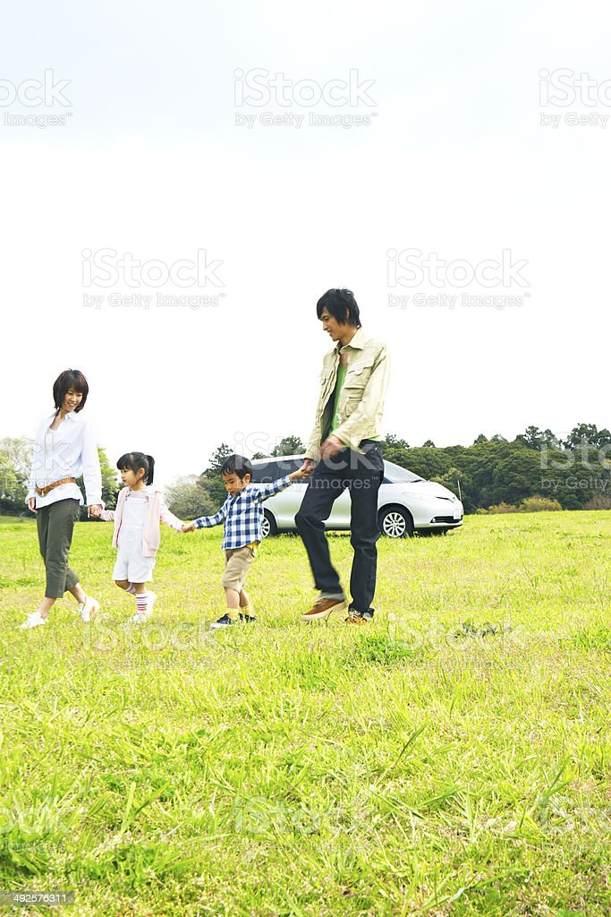 Family getting off a car and playing in prairie stock photo