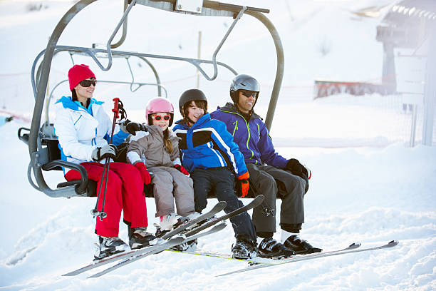 Family Getting Off Chair Lift On Ski Holiday In Mountains Family Getting Off Chair Lift On Ski Holiday In Mountains Wearing Ski Gear ski holiday stock pictures, royalty-free photos & images