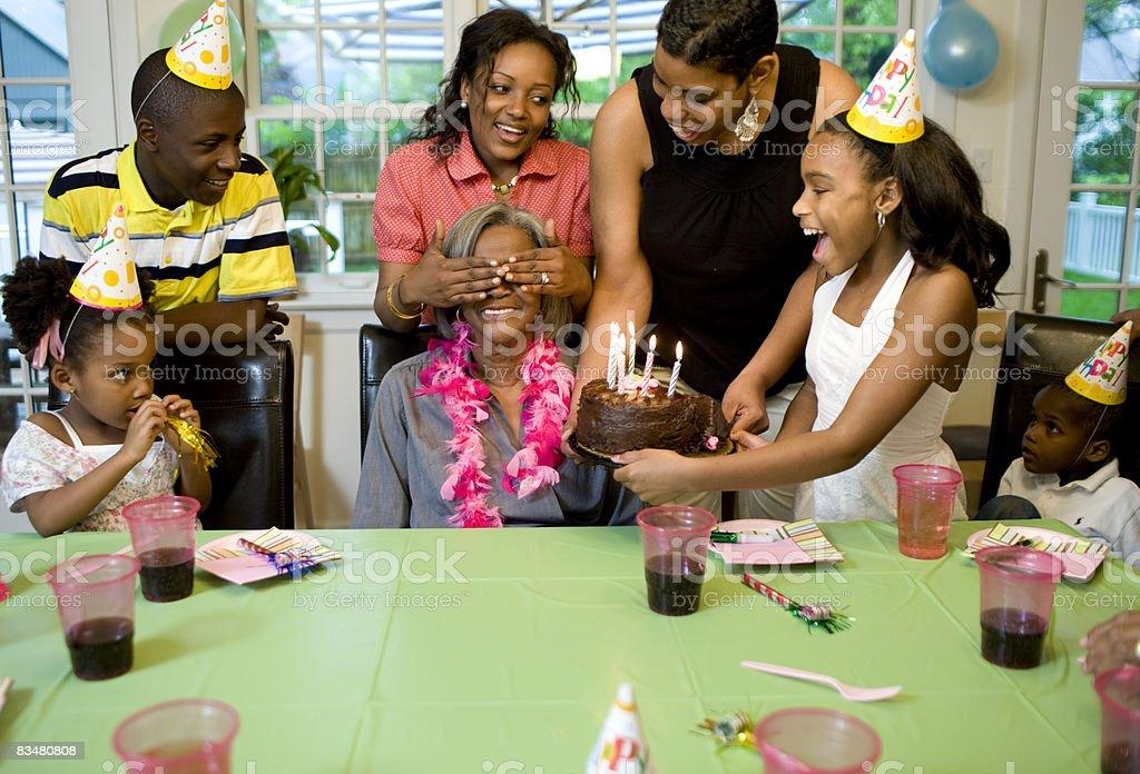 Family giving surprise party to grandmother royaltyfri bildbanksbilder