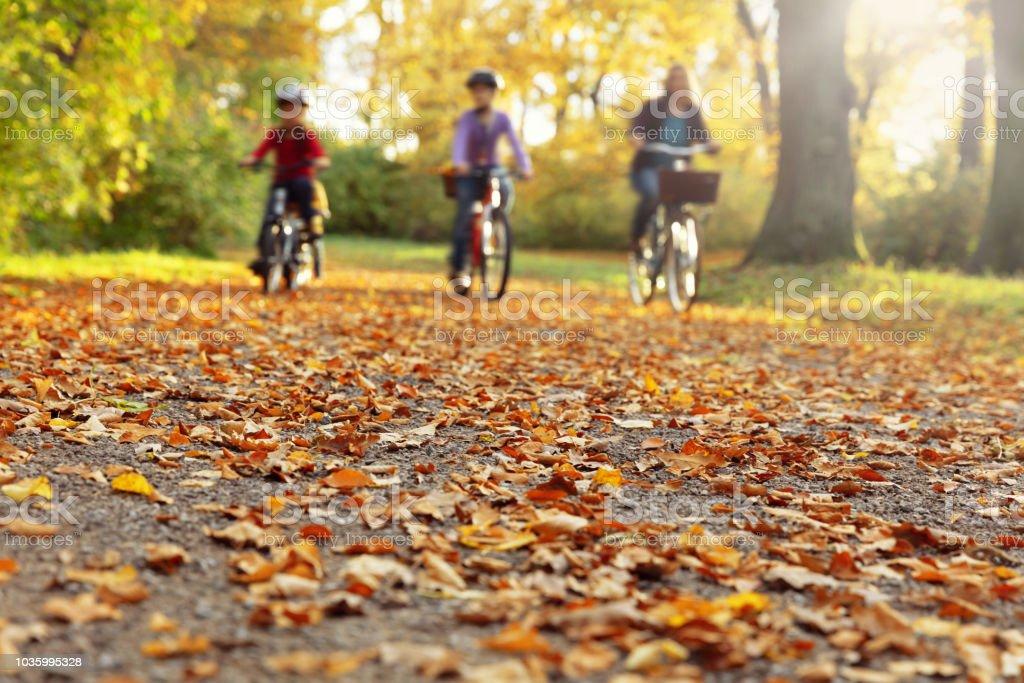 Familie geht mit dem Fahrrad durch den herbstlichen park – Foto
