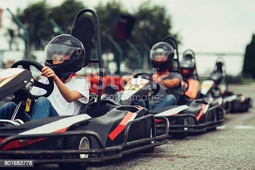 Family go-Karts together. They just finished their race on driveway.