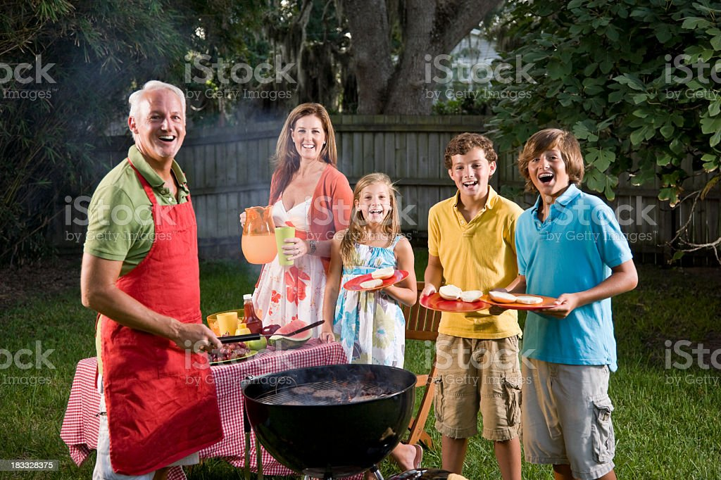 Family grilling burgers on backyard barbecue grill royalty-free stock photo