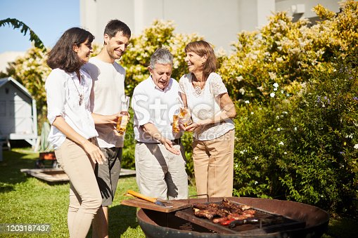 1196170672istockphoto Family grilling some food and drinking beer in Buenos Aires. 1203187437