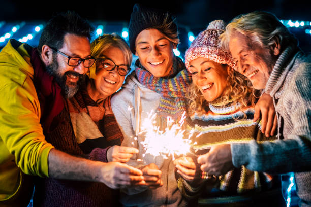 Family group celebrate together with joy the new year eve time with fire sparklers - people enjoying holidays in outdoor with cold - cheerful old and adult and young mixed generation stock photo