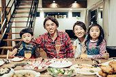 食べ物で覆われたテーブルの後ろの家族グループの写真