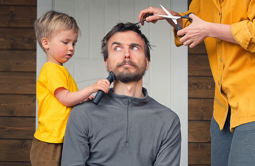 Family haircut at home during quarantine lockdown when closed all hairdressers. Mother cutting hair to father and little child boy cut dad beard with clipper. Beauty and selfcare at home lifestyle.