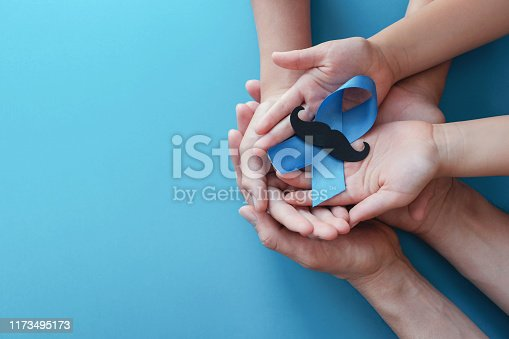 Family hands holding light blue ribbonwith mustache on blue background , Prostate Cancer Awareness, Men health awareness