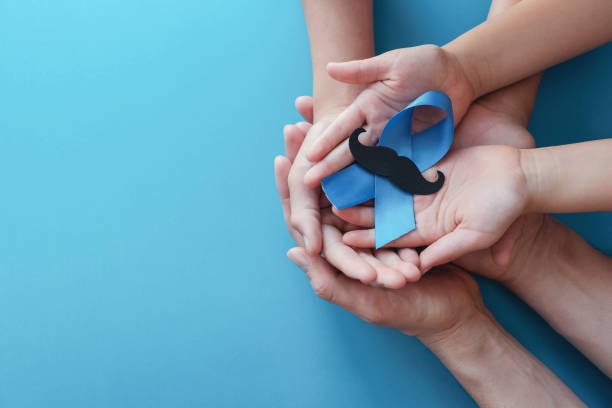 Family hands holding light blue ribbonwith mustache on blue background , Prostate Cancer Awareness, Men health awareness Family hands holding light blue ribbonwith mustache on blue background , Prostate Cancer Awareness, Men health awareness november stock pictures, royalty-free photos & images