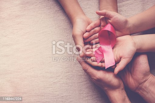 istock Family hands holding pink ribbon, breast cancer awareness, October pink concept 1163447224